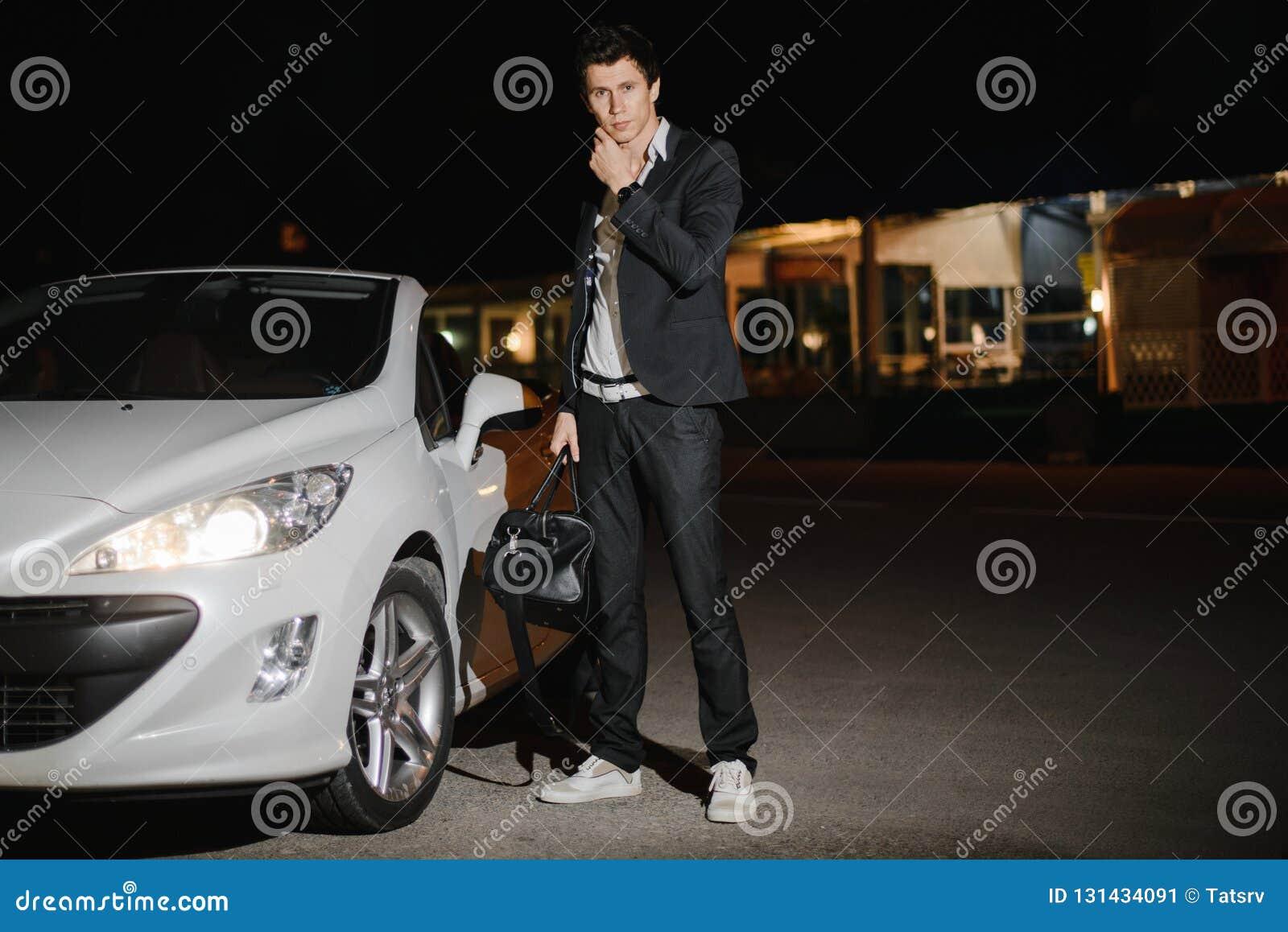 Stående av ett stiligt mananseende bredvid hans vita cabriolet uteliv Affärsman i dräkt i lyxig bil