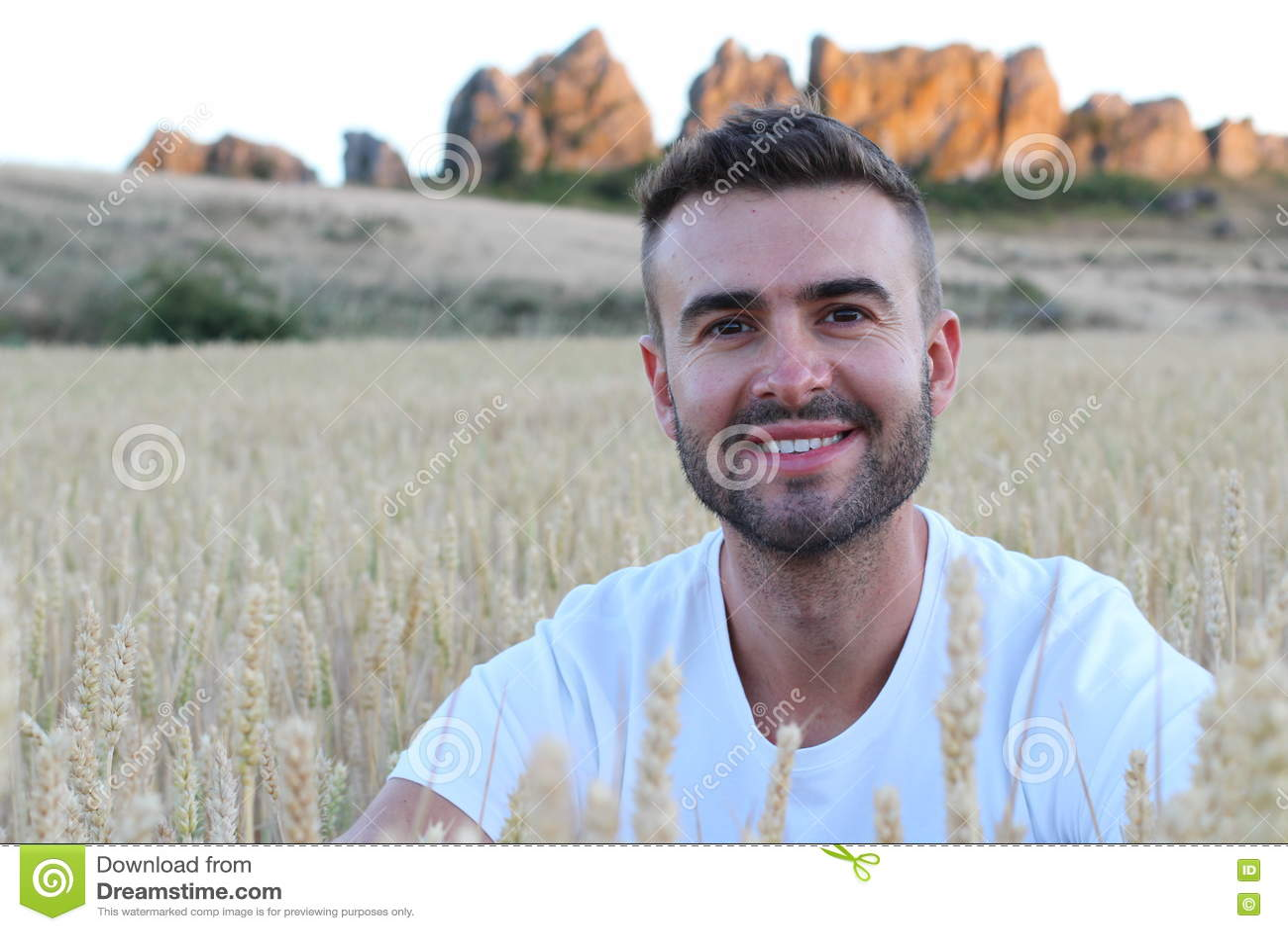 Stående av ett ungt ursnyggt naturligt mansammanträde i ett vetefält