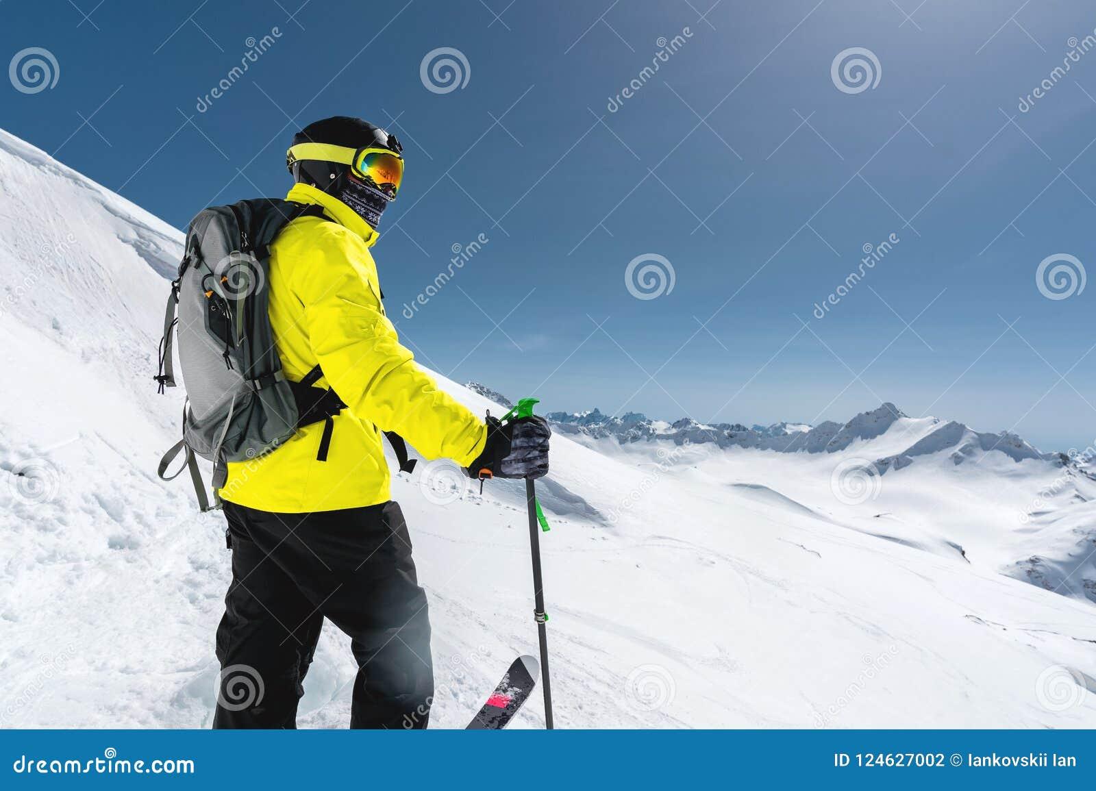 Stående av ett yrkesmässigt freerider skidåkareanseende på en snöig lutning mot bakgrunden av snö-korkade berg