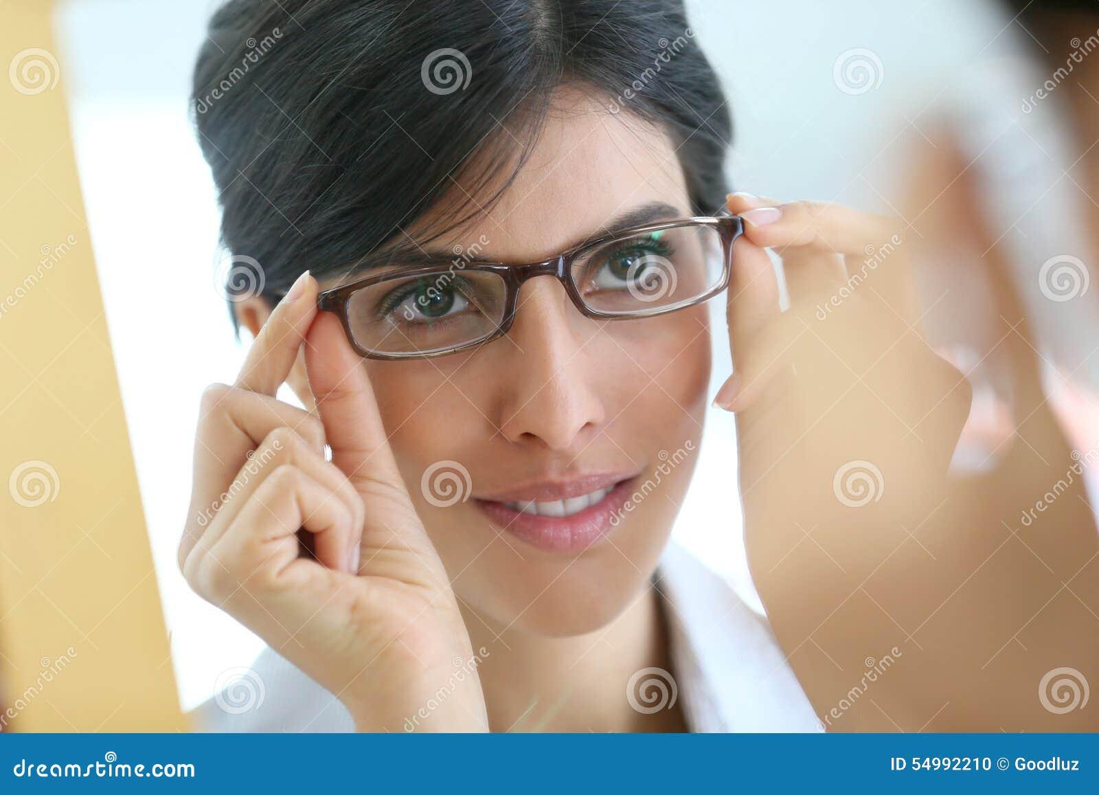 Stående av försökande glasögon för ung kvinna på
