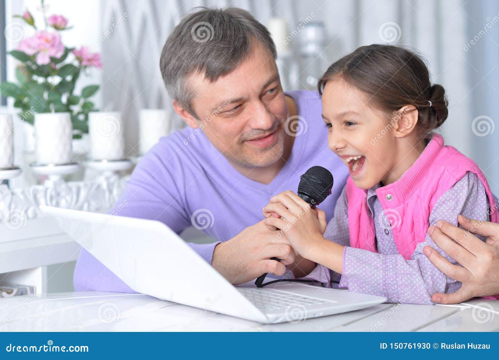 Stående av fadern med den lilla dottern som sjunger karaoke