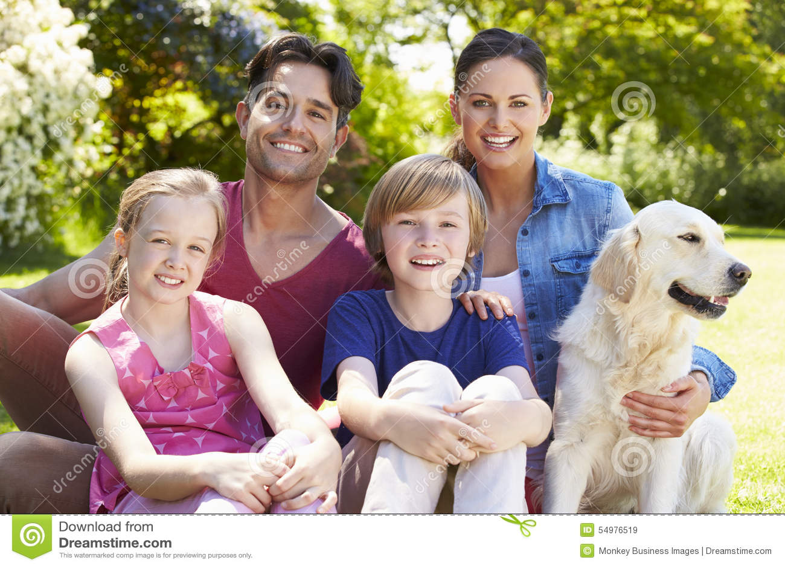 Stående av familjen med hunden som kopplar av i sommarträdgård