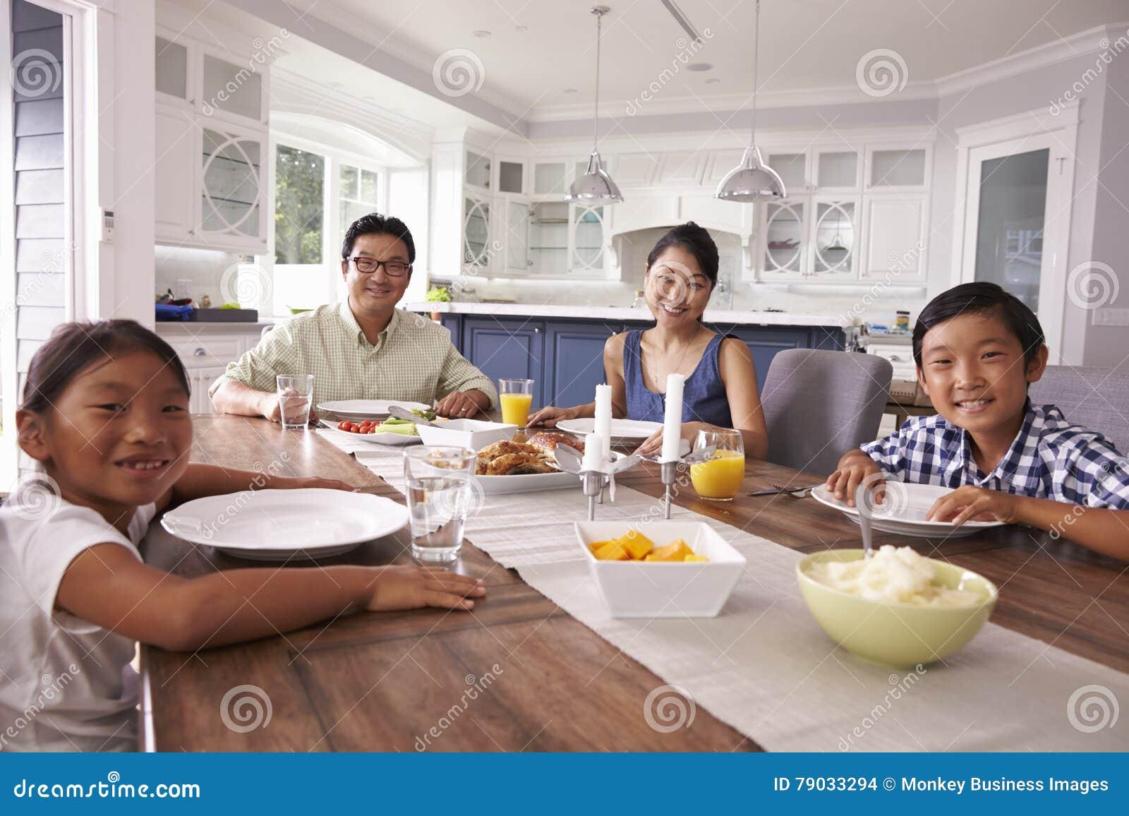Stående av familjen som hemma äter mål tillsammans