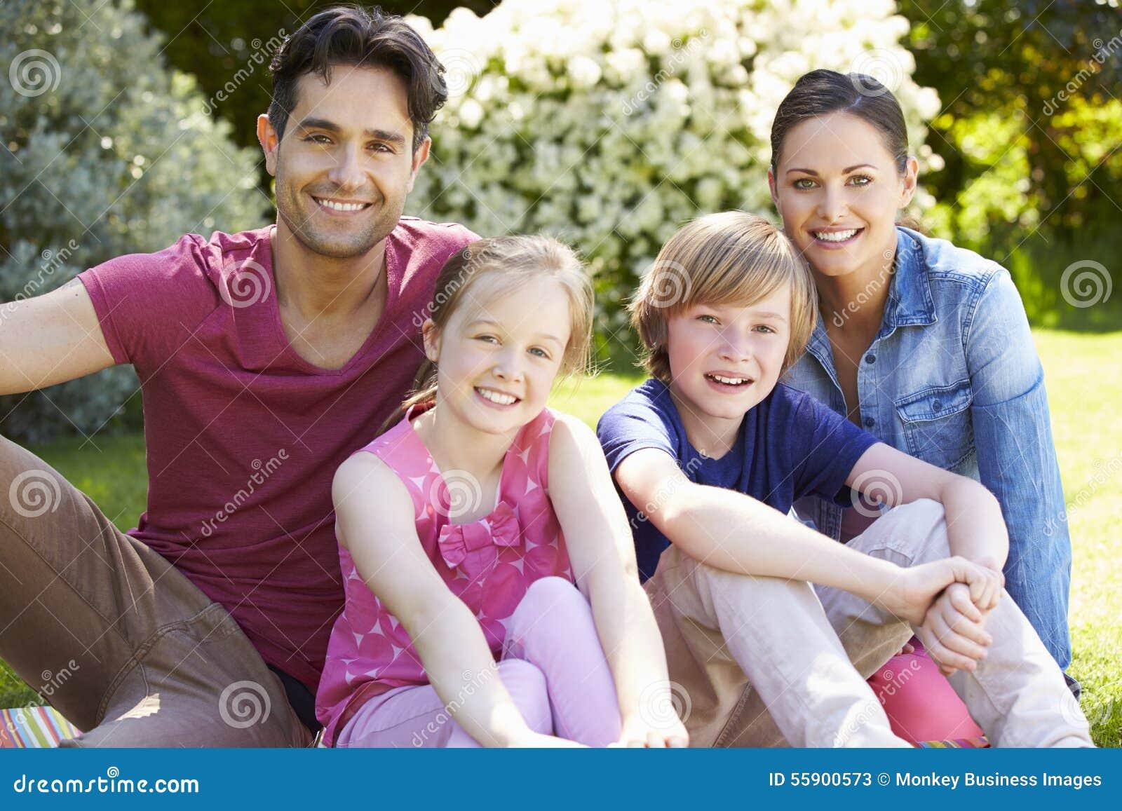 Stående av familjen som kopplar av i sommarträdgård