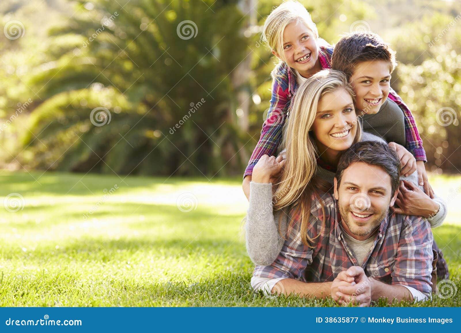 Stående av familjen som ligger på gräs i bygd