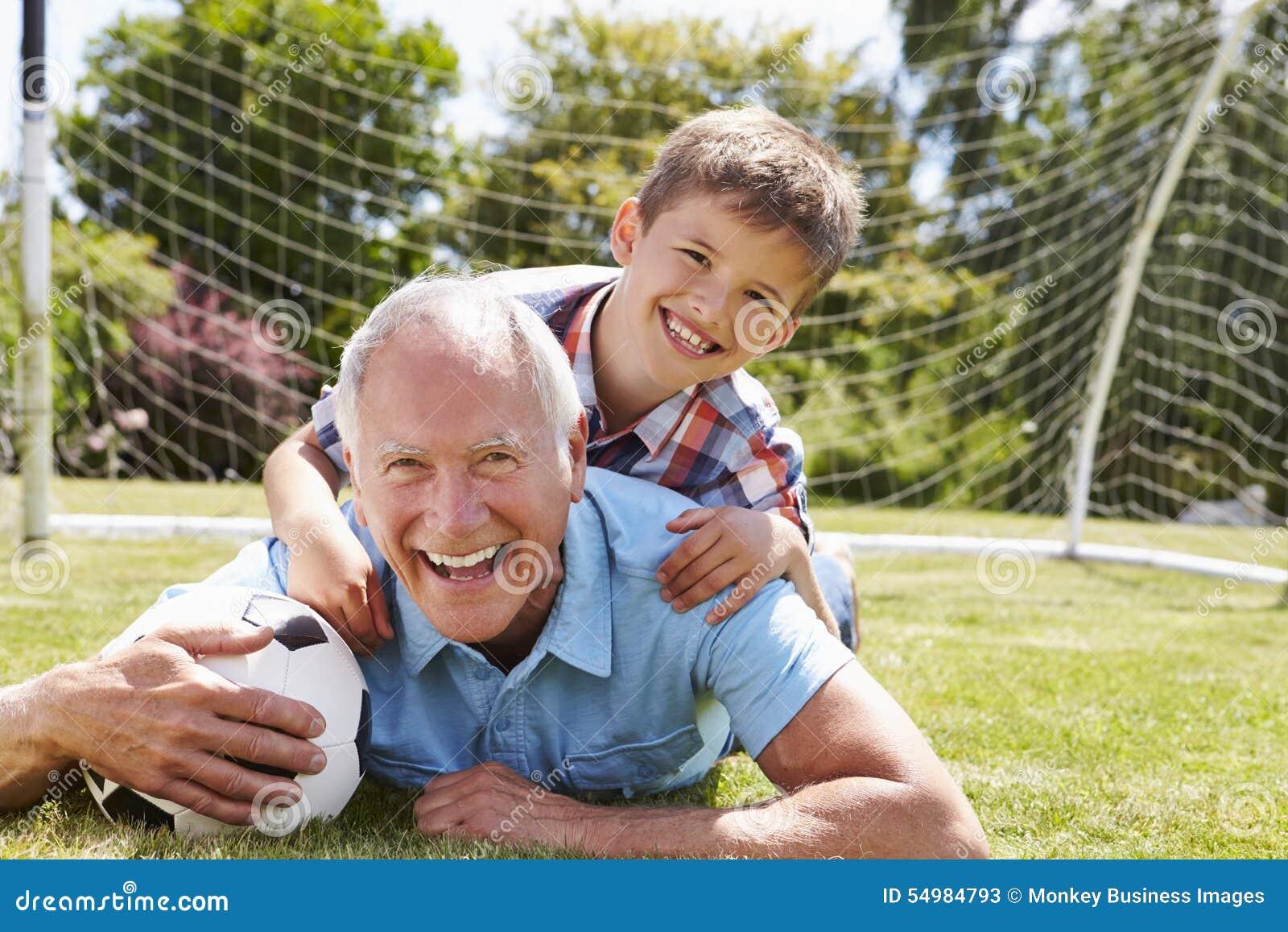 Stående av farfadern och sonsonen med fotboll