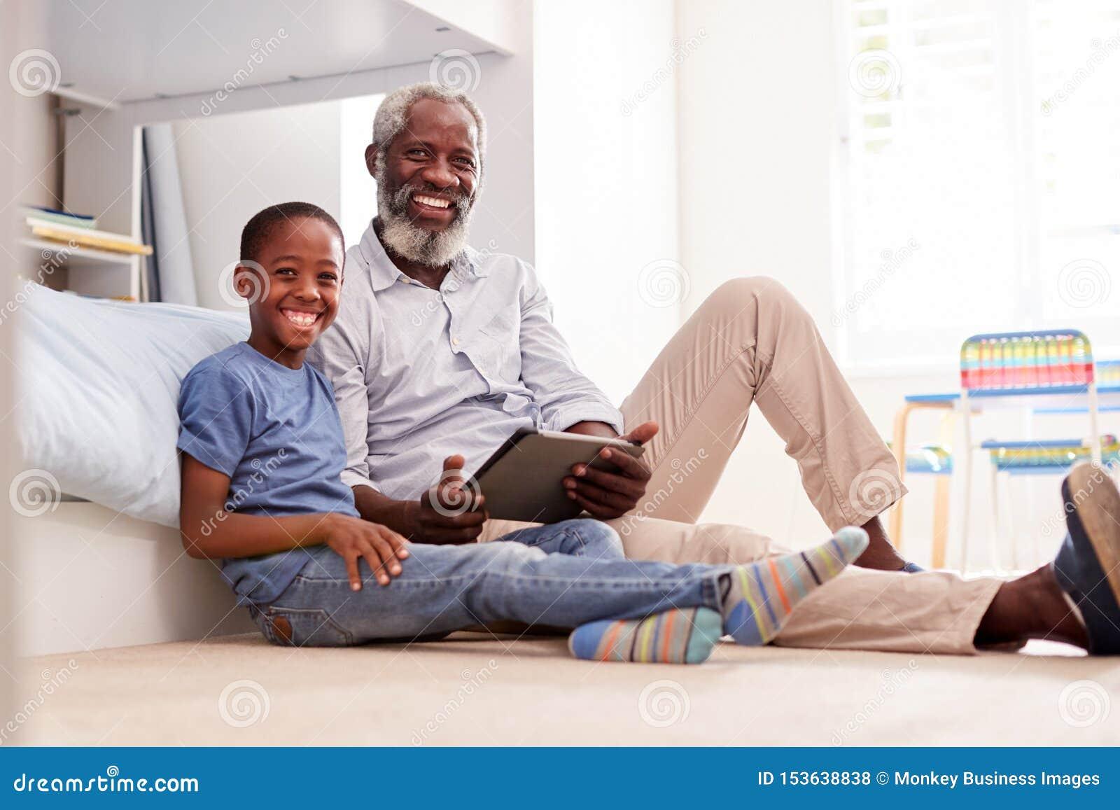 Stående av farfadern som sitter med sonsonen i det Childs sovrummet genom att använda den Digital minnestavlan tillsammans