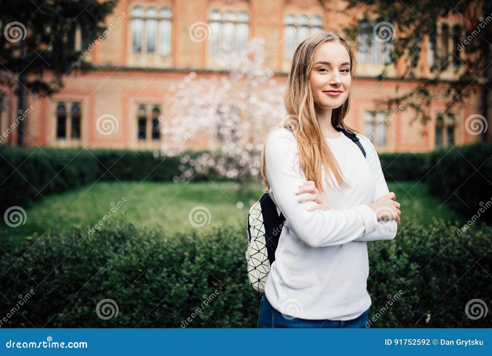 Stående av flickauniversitetsstudenten utomhus på universitetsområde