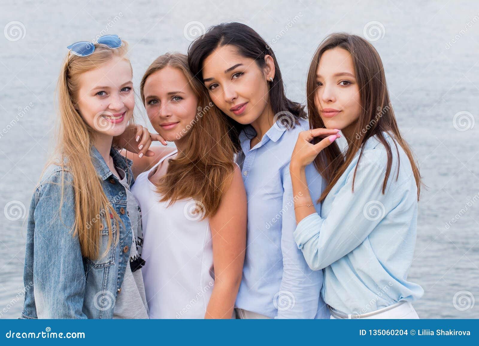 Stående av fyra unga kvinnliga vänner som går på havskusten som ser att skratta för kamera