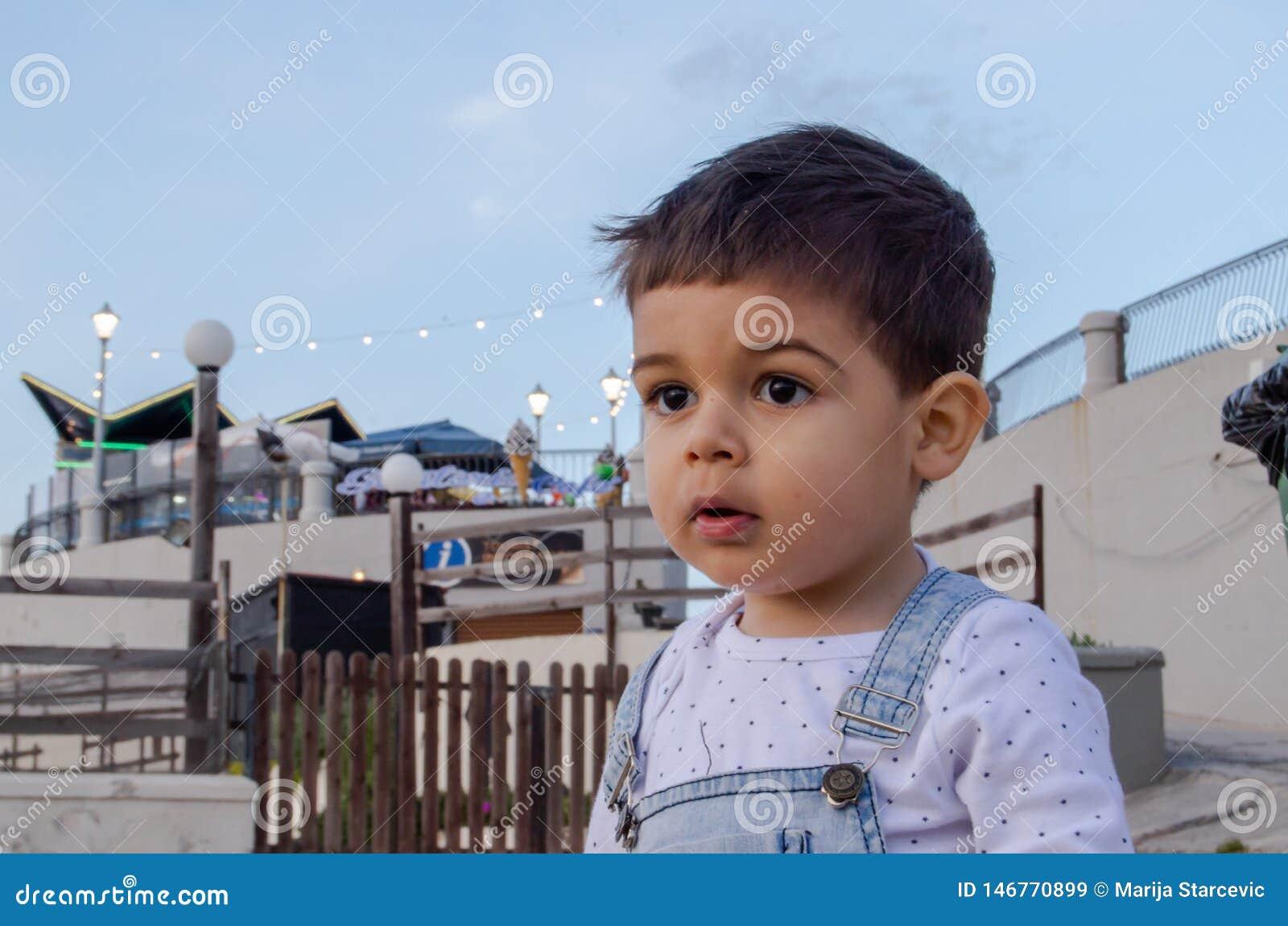 Stående av gulliga två år gammalt pojkemörker att höra