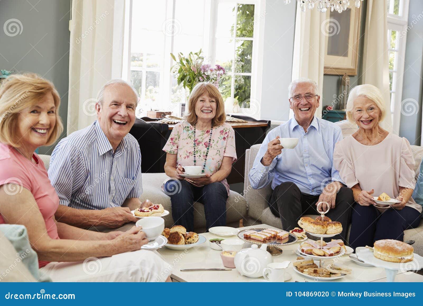 Stående av höga vänner som hemma tycker om eftermiddagte
