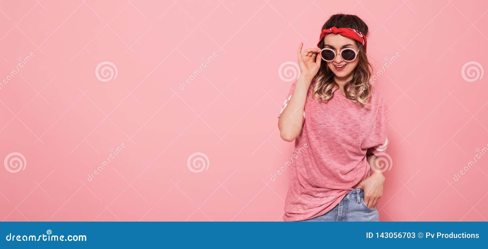 Stående av hipsterflickan i exponeringsglas på rosa bakgrund