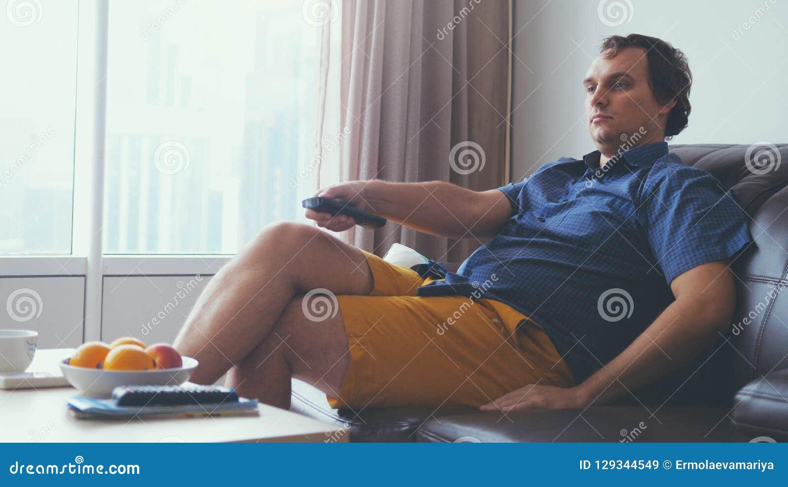 Stående av koncentrerat sammanträde för ung man på soffan i vardagsrum och hållande ögonen på intressant tv att programmera