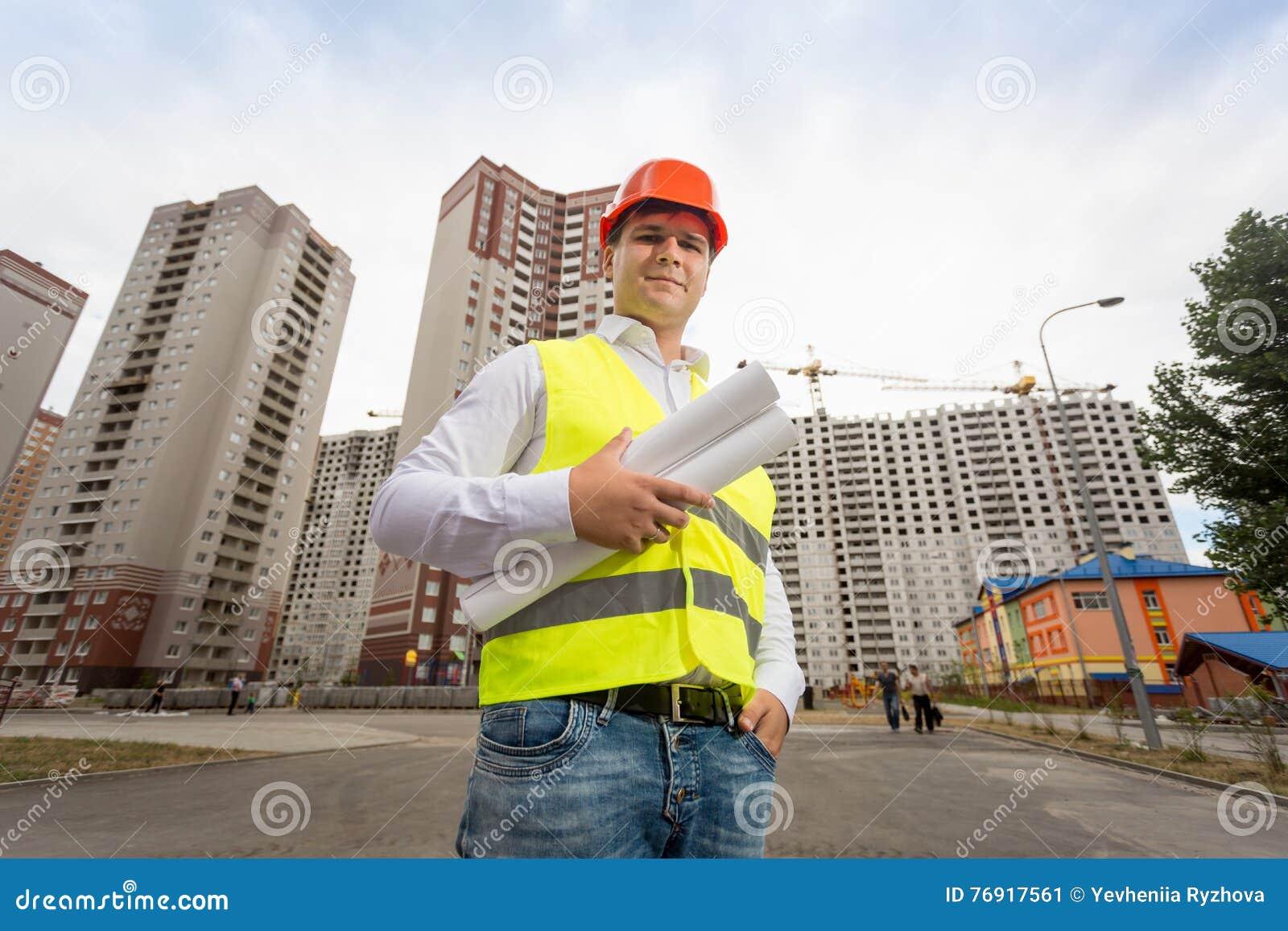 Stående av konstruktionsteknikern i hardhaten som framme poserar av