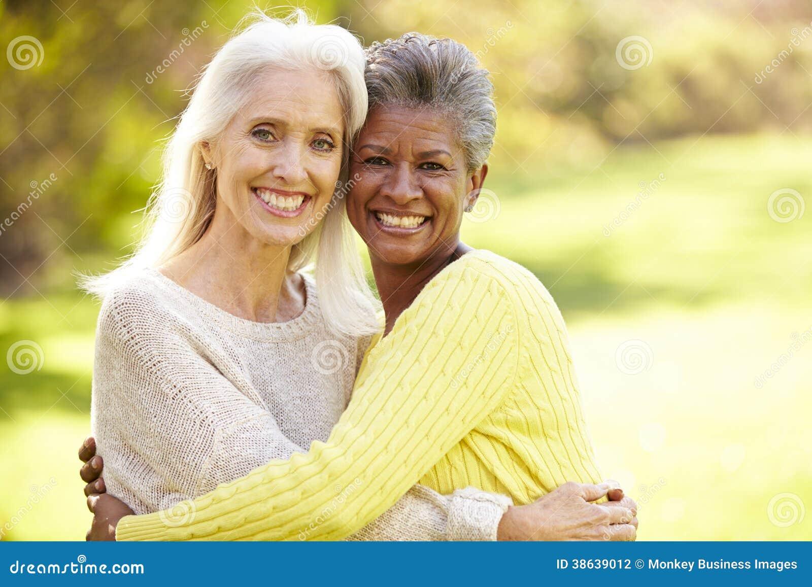 Stående av krama för två moget kvinnligt vänner