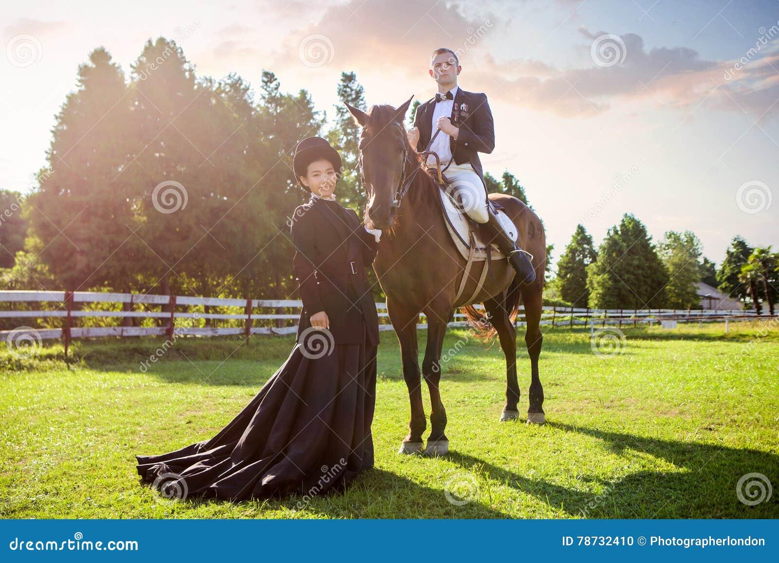 Stående av kvinnaanseendet vid mansammanträde på häst på fältet under solnedgång