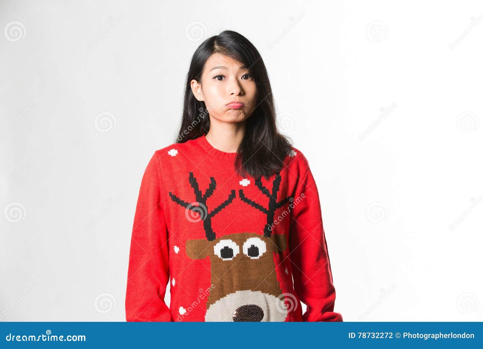 Stående av kvinnan i framsida för stående danande för jultröja rolig över grå bakgrund