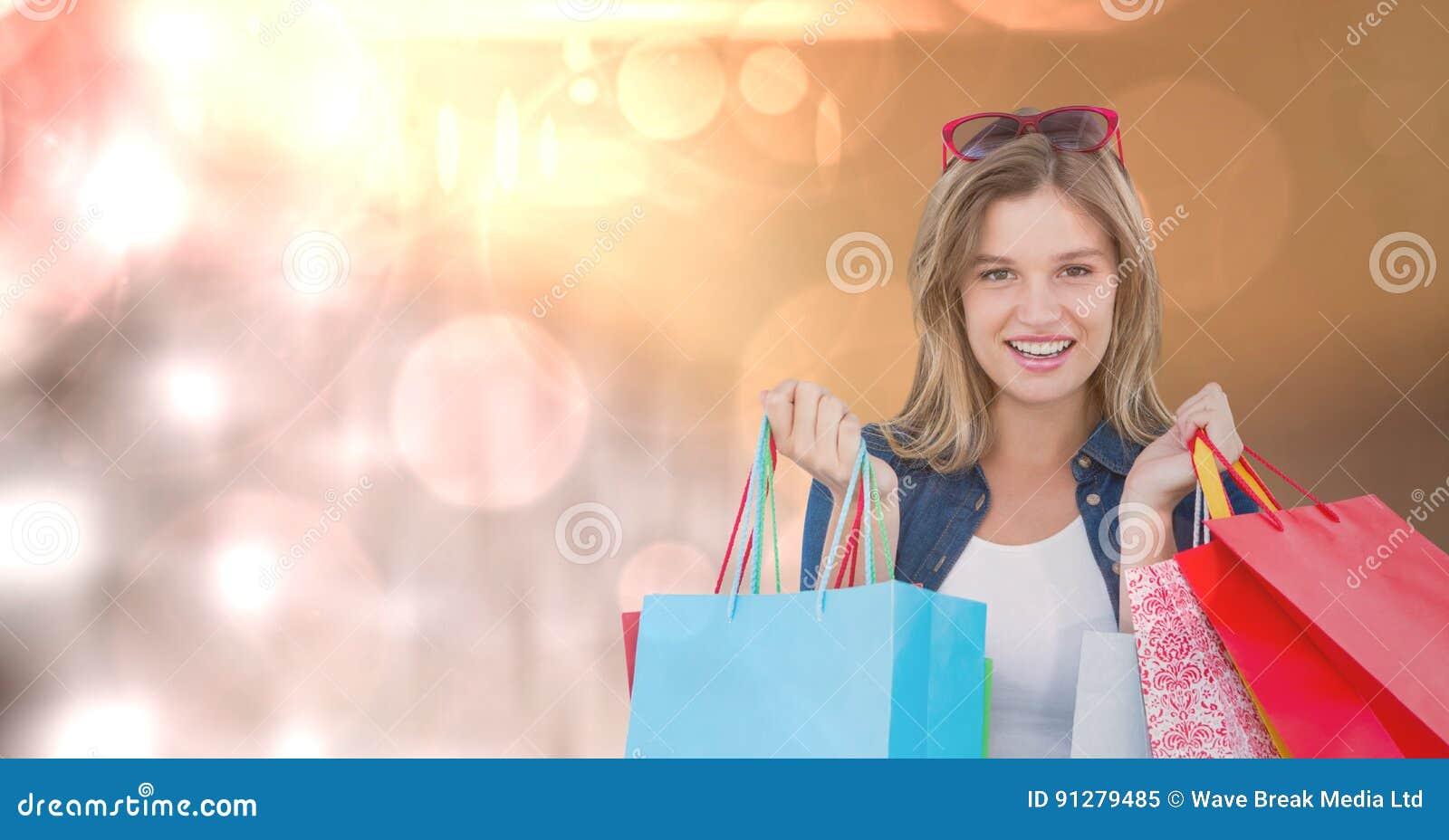 Stående av kvinnan med bärande shoppingpåsar över bokeh