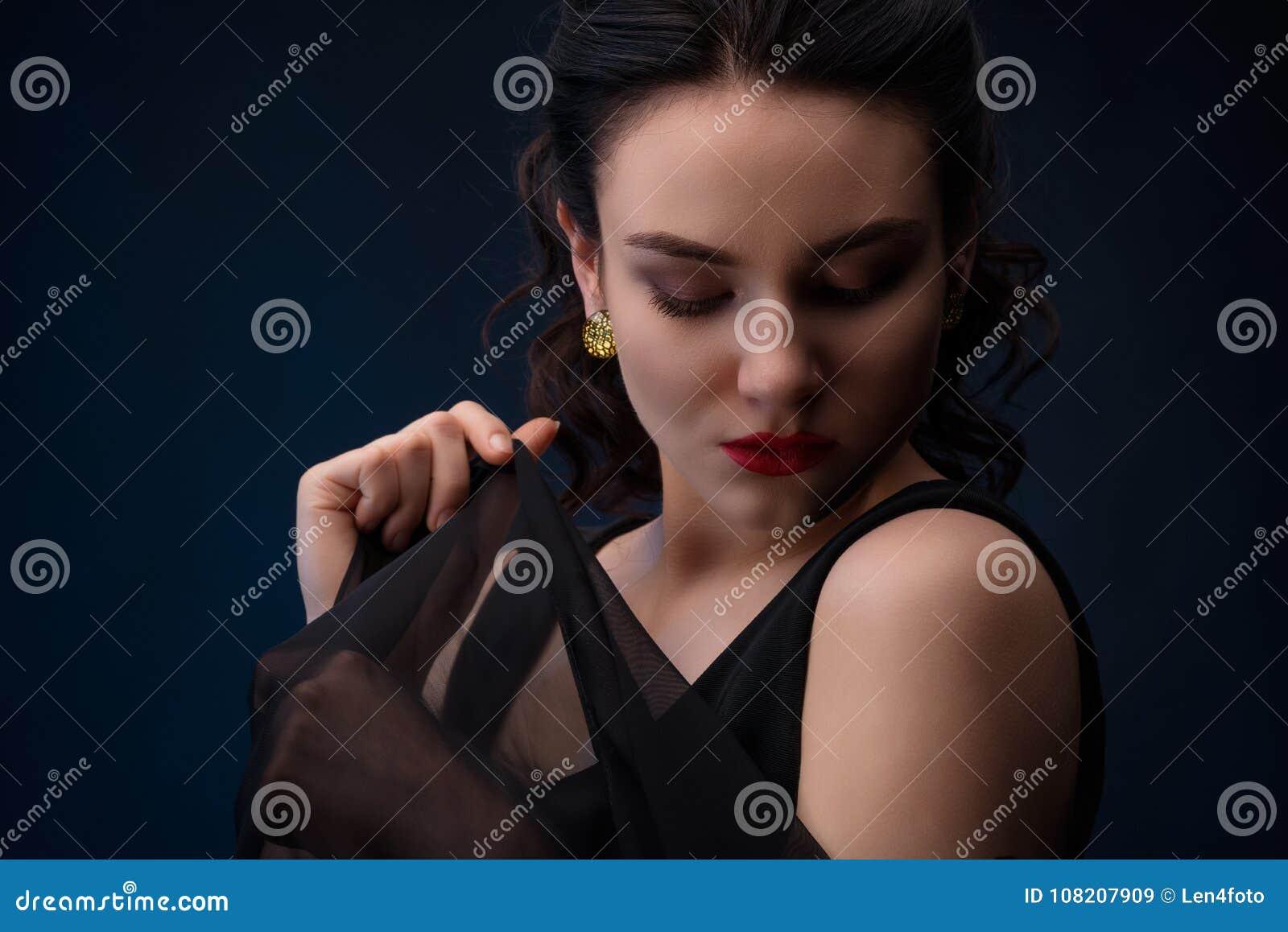 Stående av kvinnan som ner ser med stycket av tyll