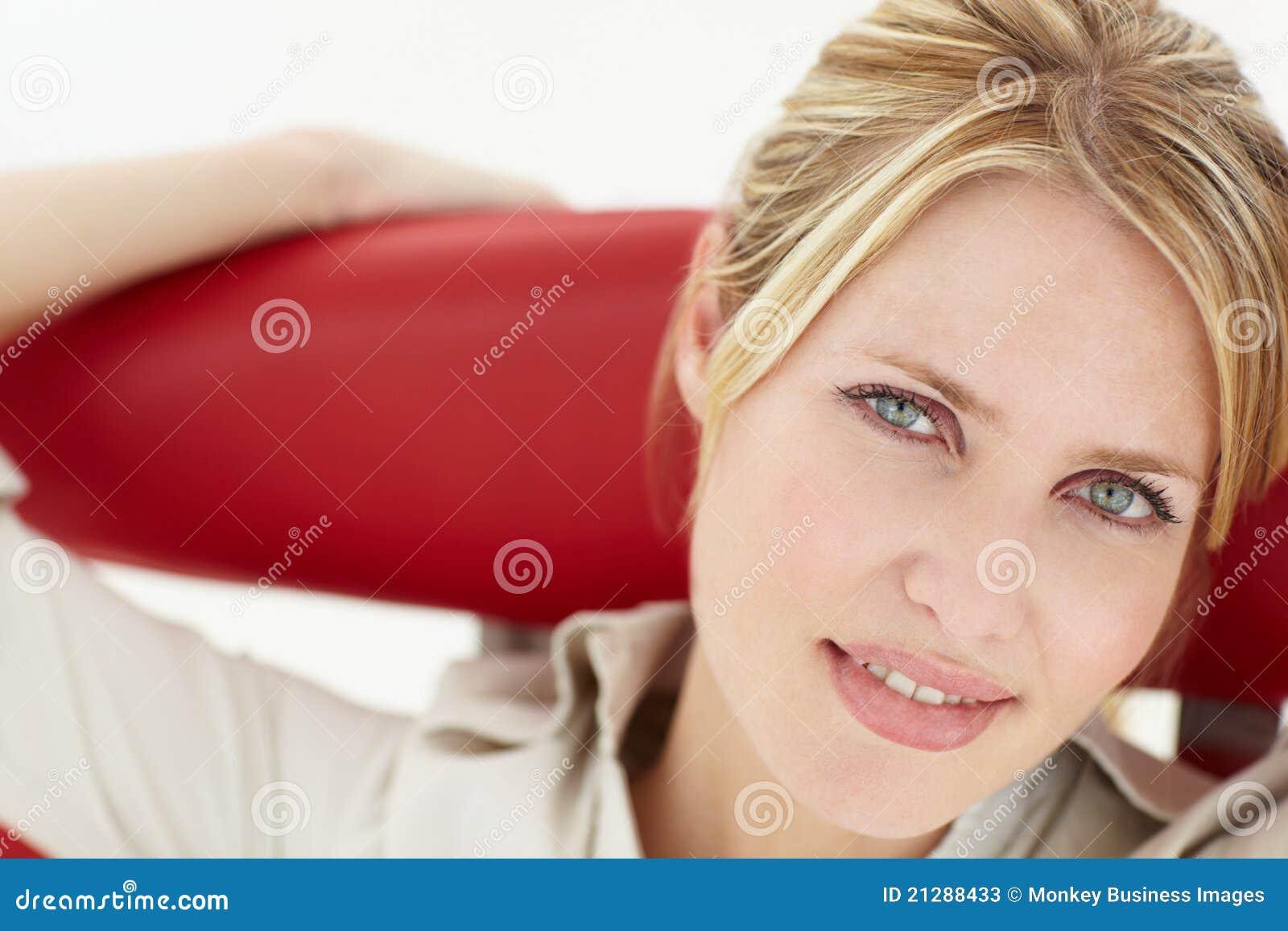 Stående av kvinnan som sitter i stol