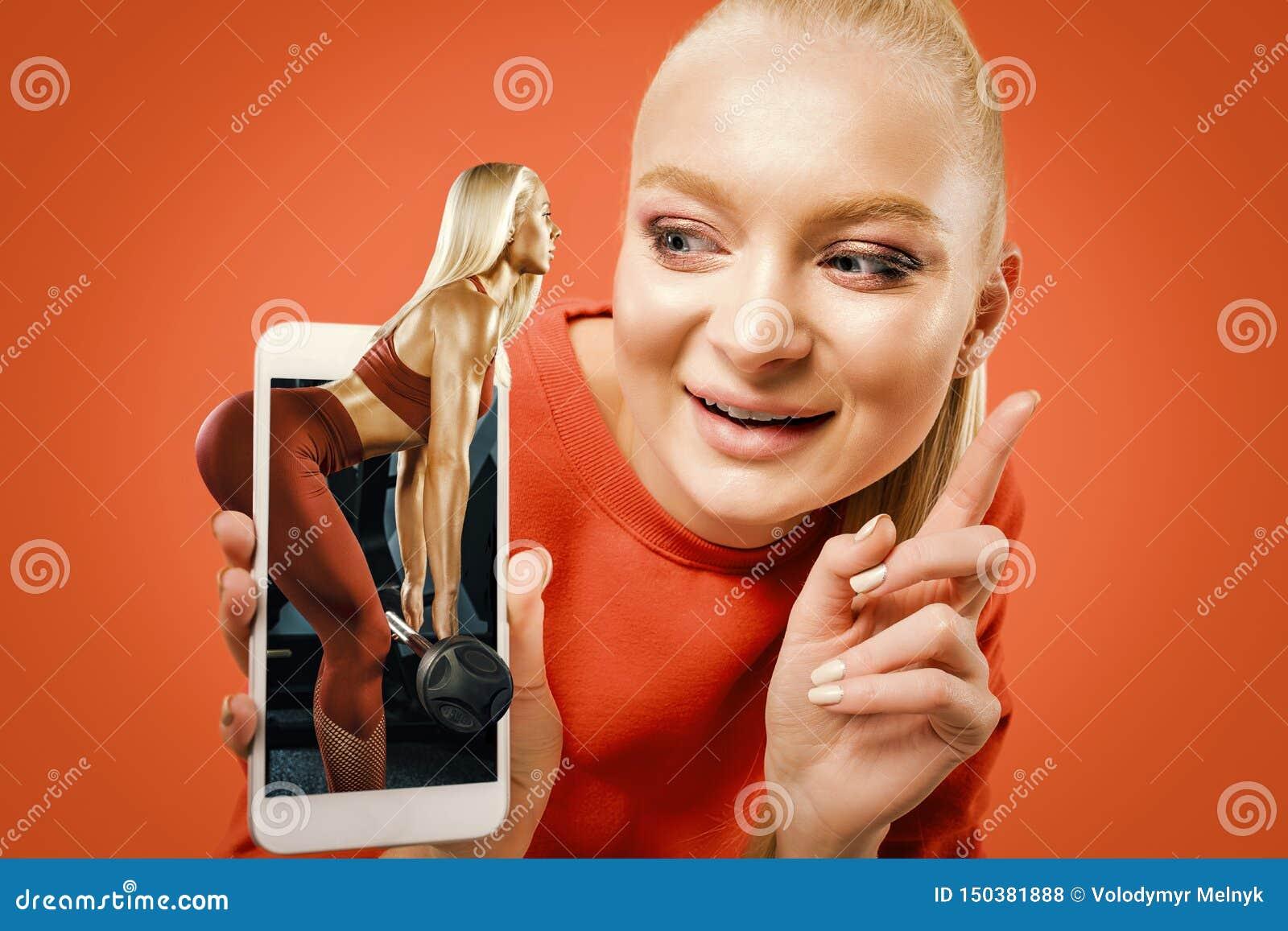 Stående av kvinnavisningskärmen av mobiltelefonen som isoleras över orange bakgrund