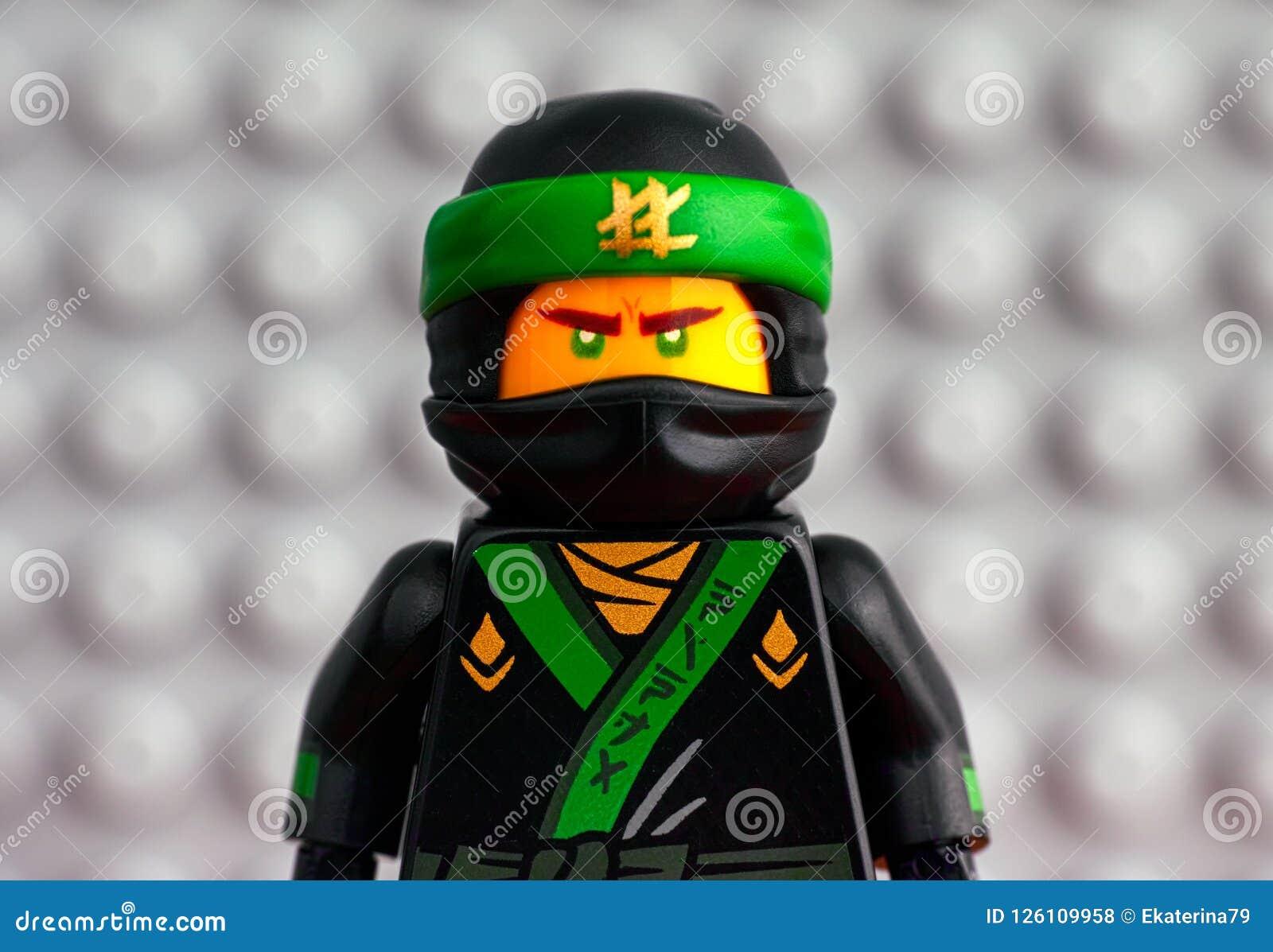 Stående av Lego The Green Ninja mot grå baseplatebackgrou
