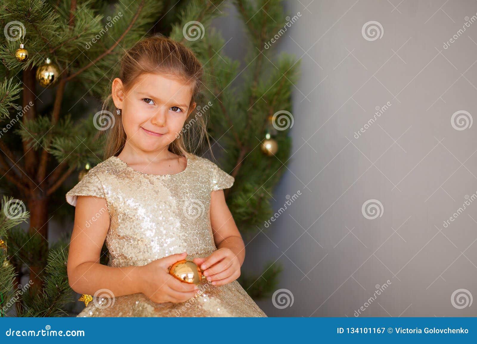 Stående av lilla flickan med julträdet