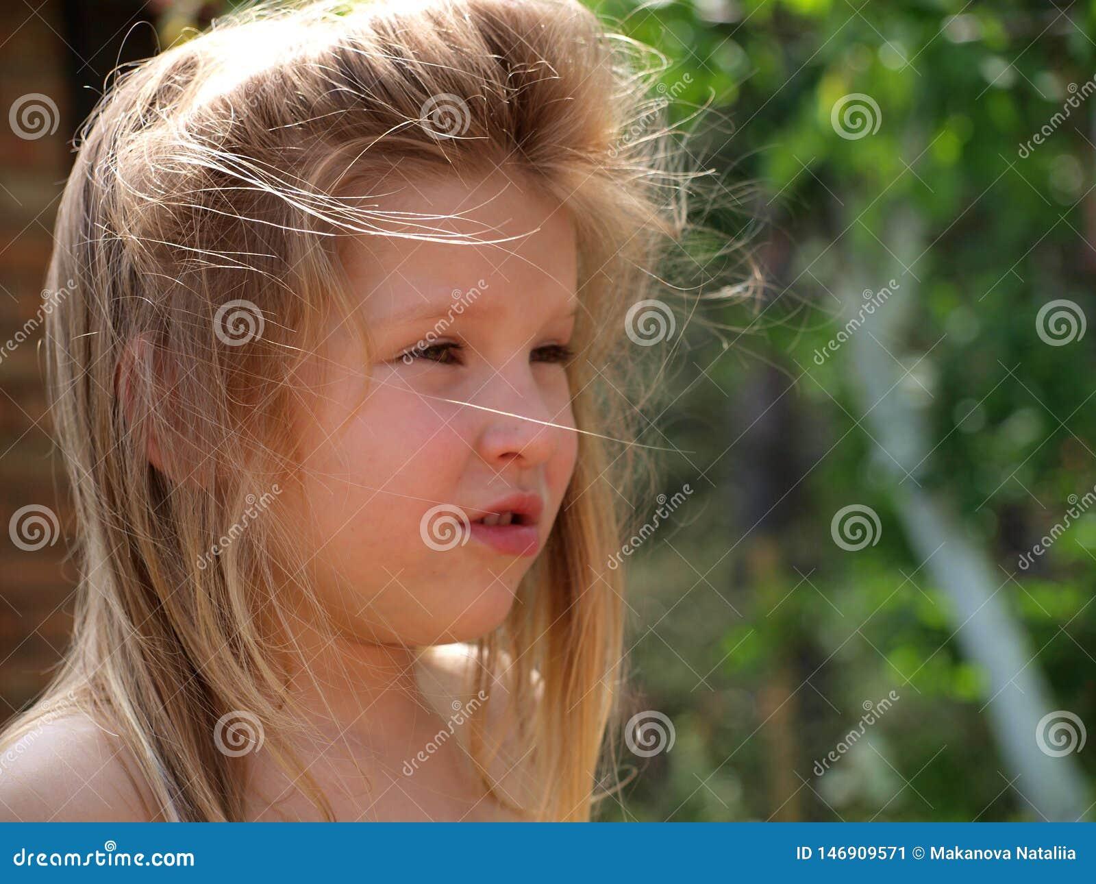 Stående av lite flickan med blont hår som rufsas till av vinden