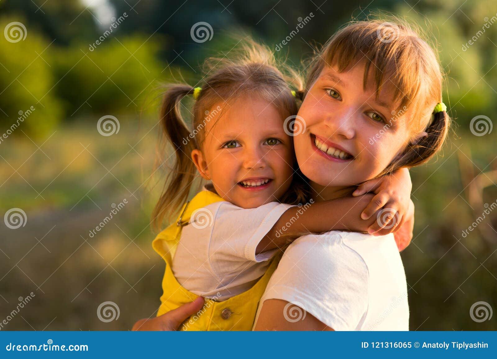 Stående av lite flickan med den äldre systern som är tonårig i natur