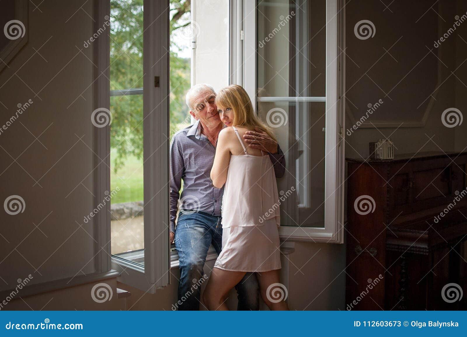 Stående av lyckliga par med ålderskillnadanseende nära fönstret i deras hem under varm dag för sommar Psykologi av