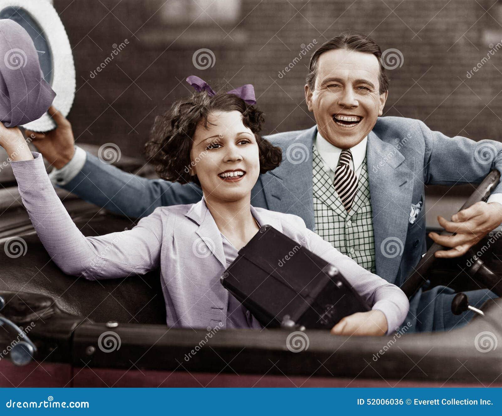 Stående av lyckliga par som vinkar i bil (alla visade personer inte är längre uppehälle, och inget gods finns Leverantörgarantier