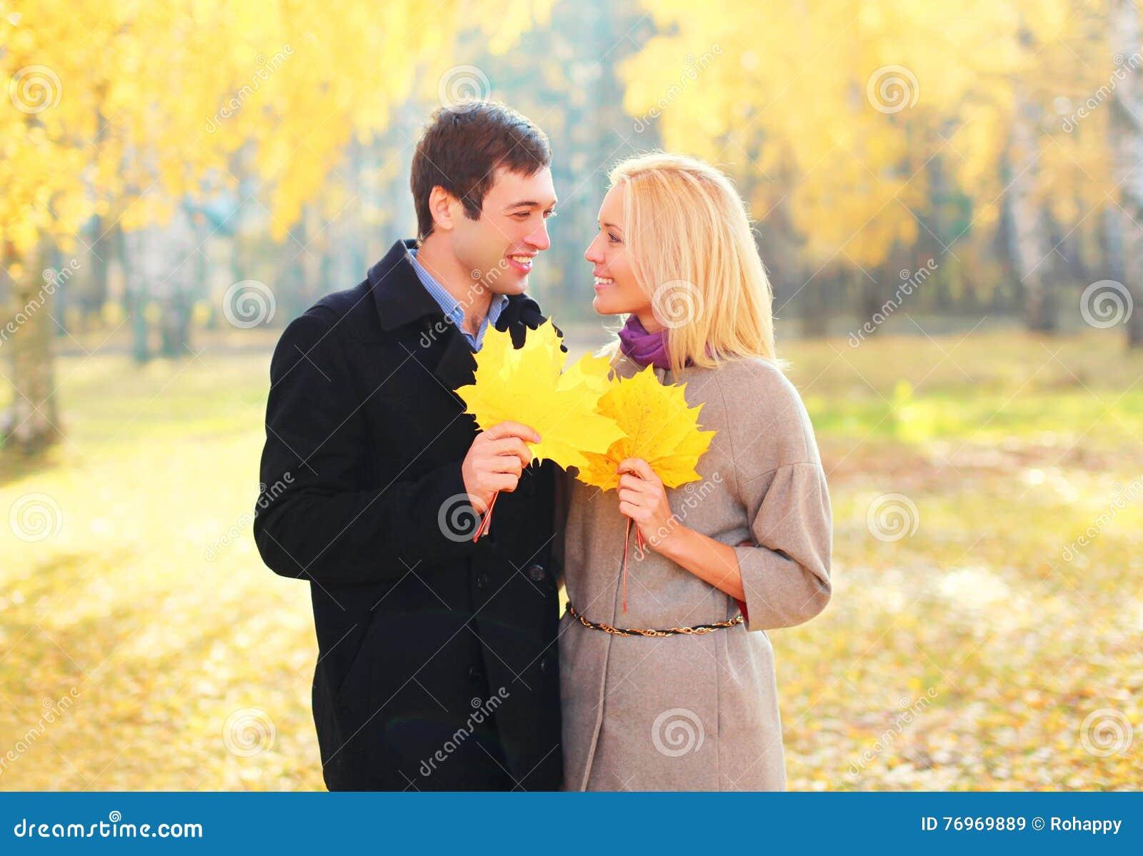 Stående av lyckliga unga le par med gula lönnblad i varmt soligt