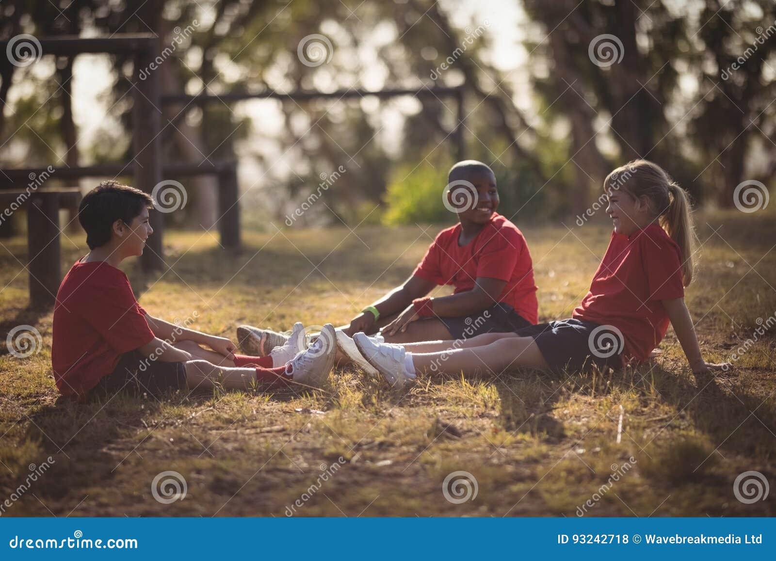 Stående av lyckliga ungar som kopplar av på gräs under hinderkurs