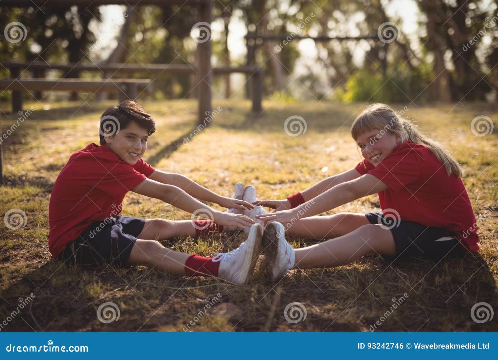 Stående av lyckliga ungar som utför sträcka övning under hinderkurs