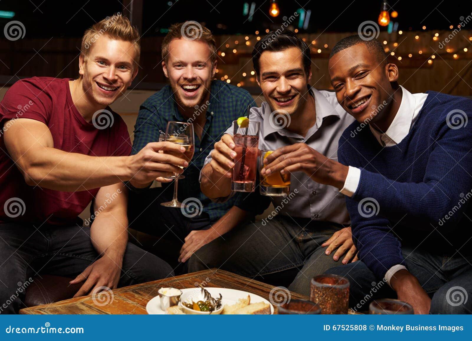 Stående av manliga vänner som ut tycker om natt på takstången