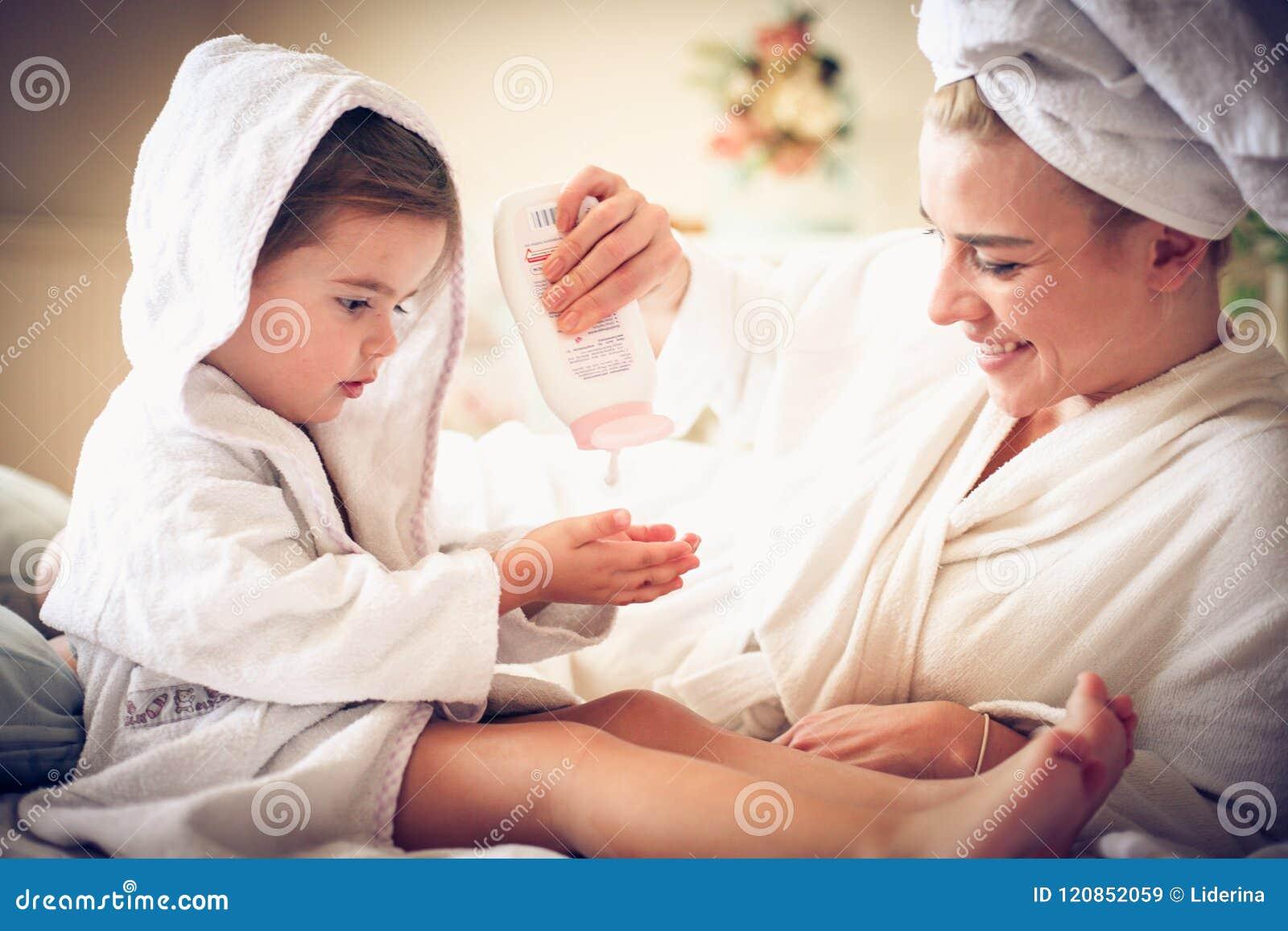Stående av modern och dottern efter badet som applicerar kropplotion