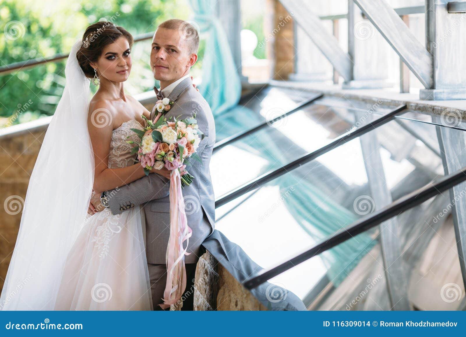 Stående av nygifta personer på bröllopdag Brudgummen i en grå dräkt med en vit skjorta och en fluga kramar en härlig brud