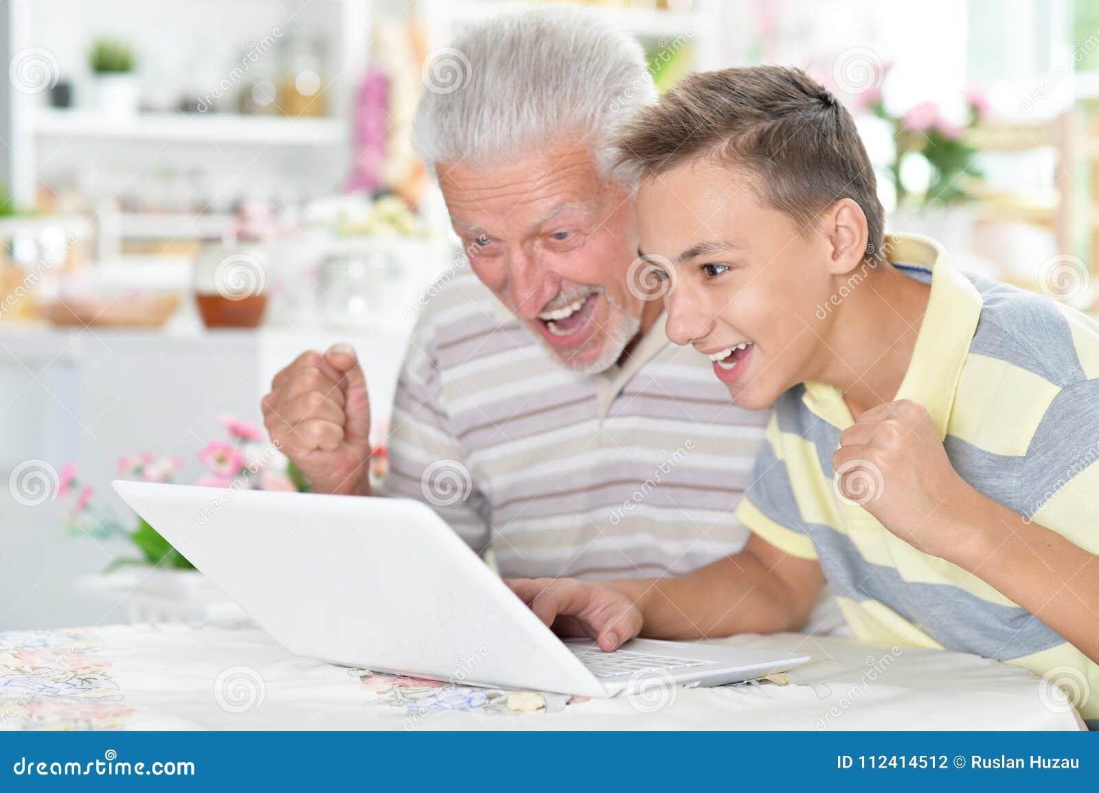 Stående av pojken och farfadern med en bärbar dator