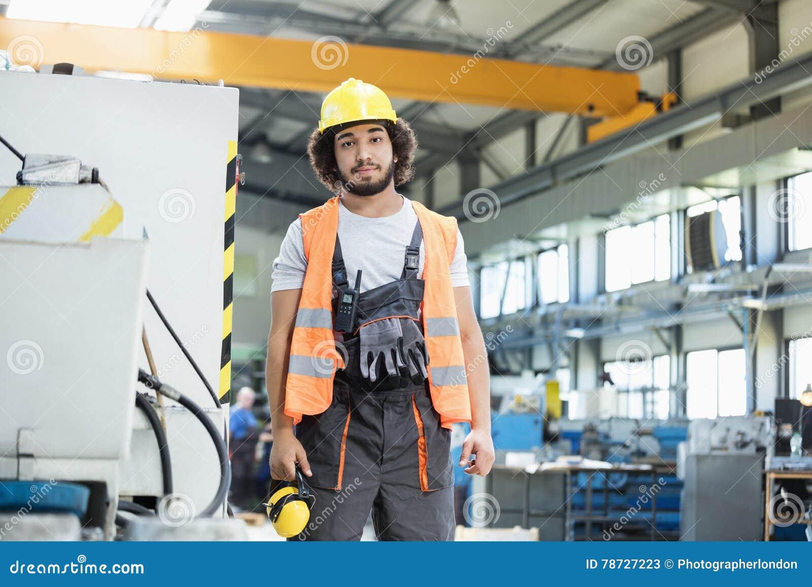 Stående av säker bärande skyddskläder för manuell arbetare i metallbransch