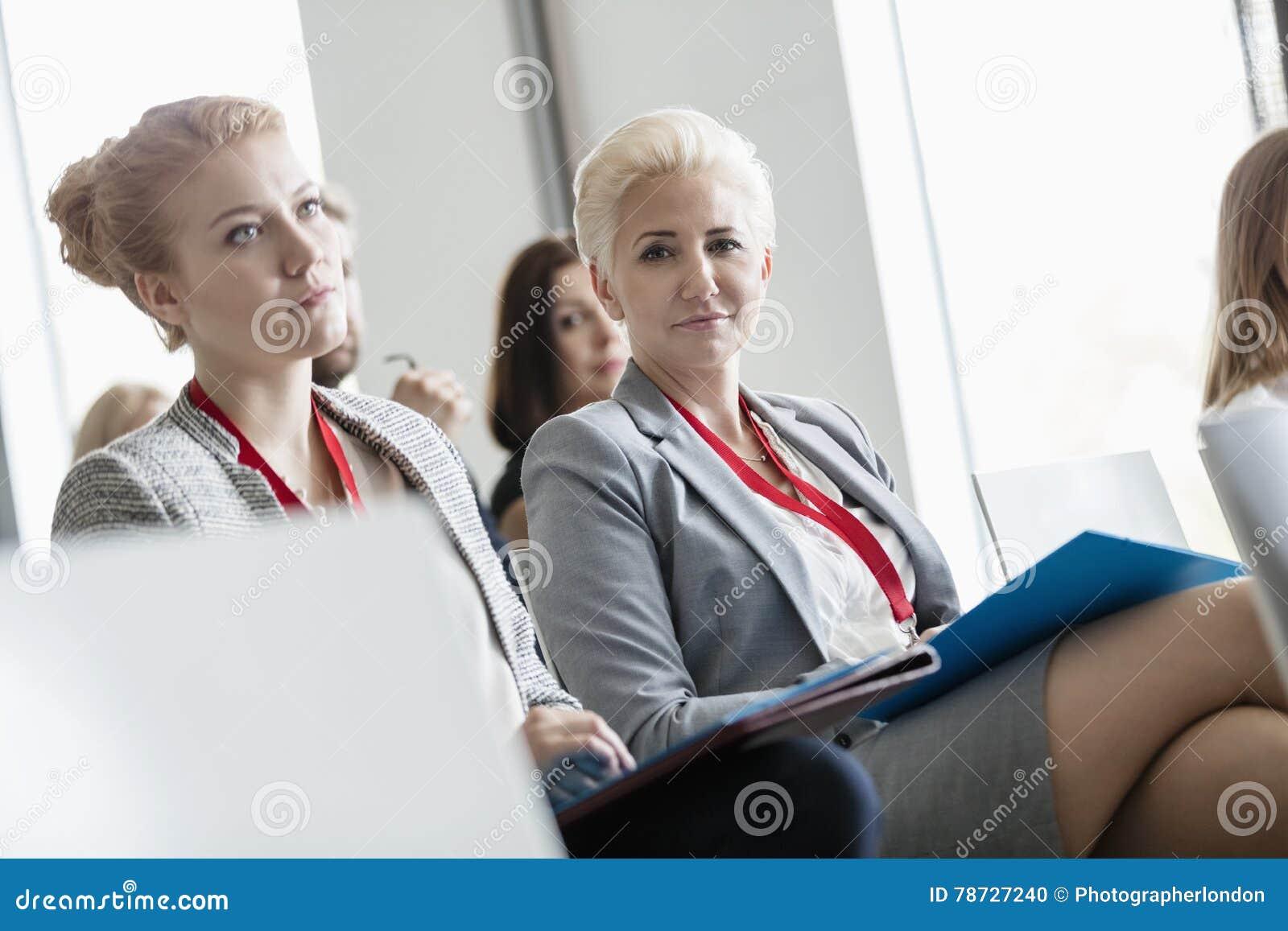 Stående av säkert affärskvinnasammanträde i seminariumkorridor