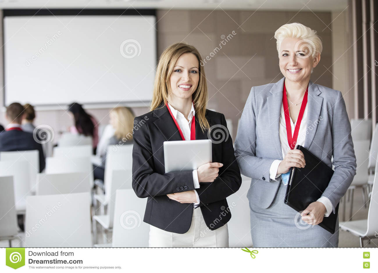 Stående av säkra affärskvinnor som står i seminariumkorridor