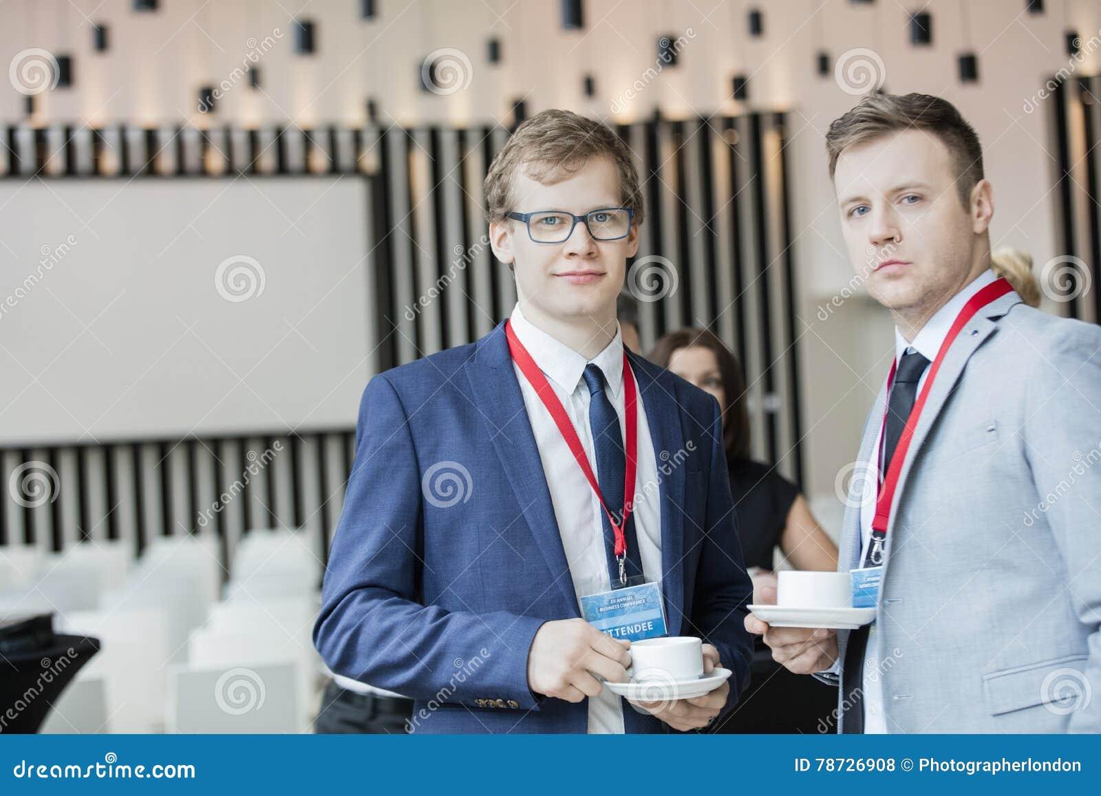 Stående av säkra affärsmän som rymmer kaffekoppar i konventcentrum