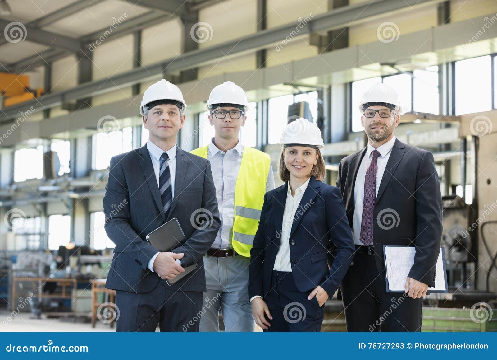 Stående av säkra bärande hardhats för affärsfolk i metallbransch
