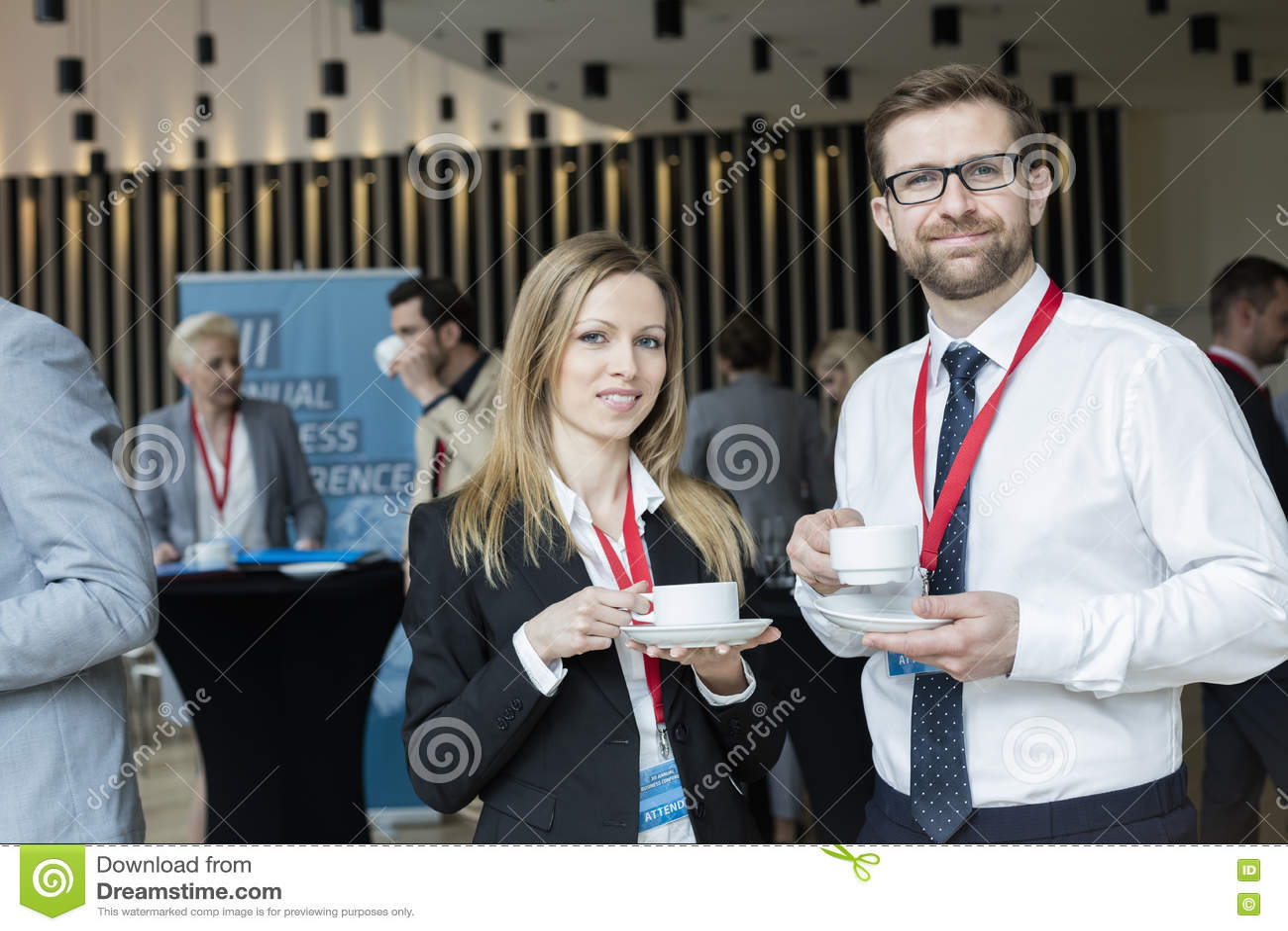 Stående av säkra koppar för kaffe för affärsfolk hållande på lobbyen i konventcentrum