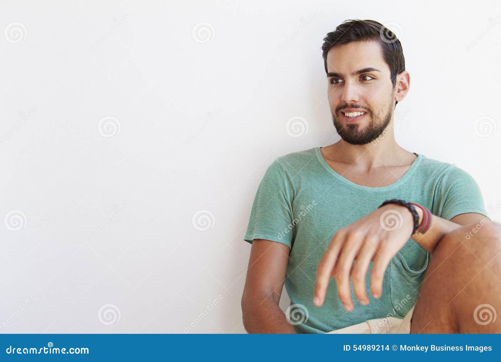 Stående av sammanträde för ung man mot den vita väggen