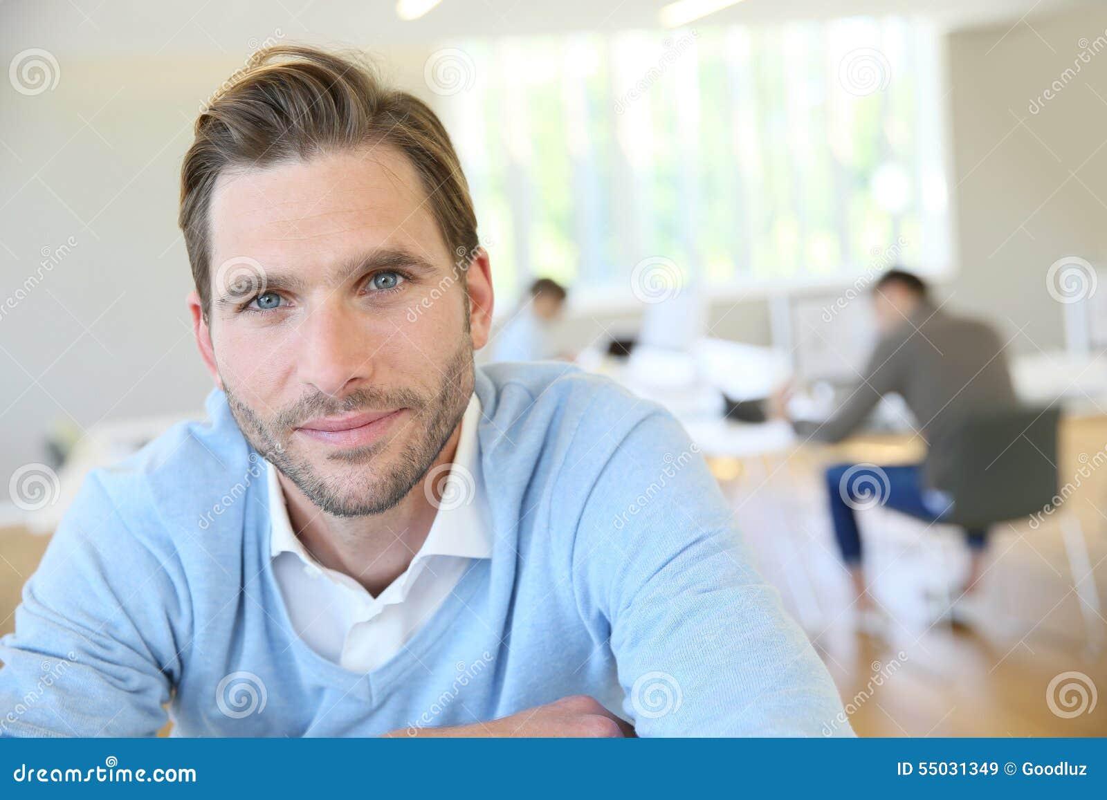 Stående av sammanträde för ung man på kontoret