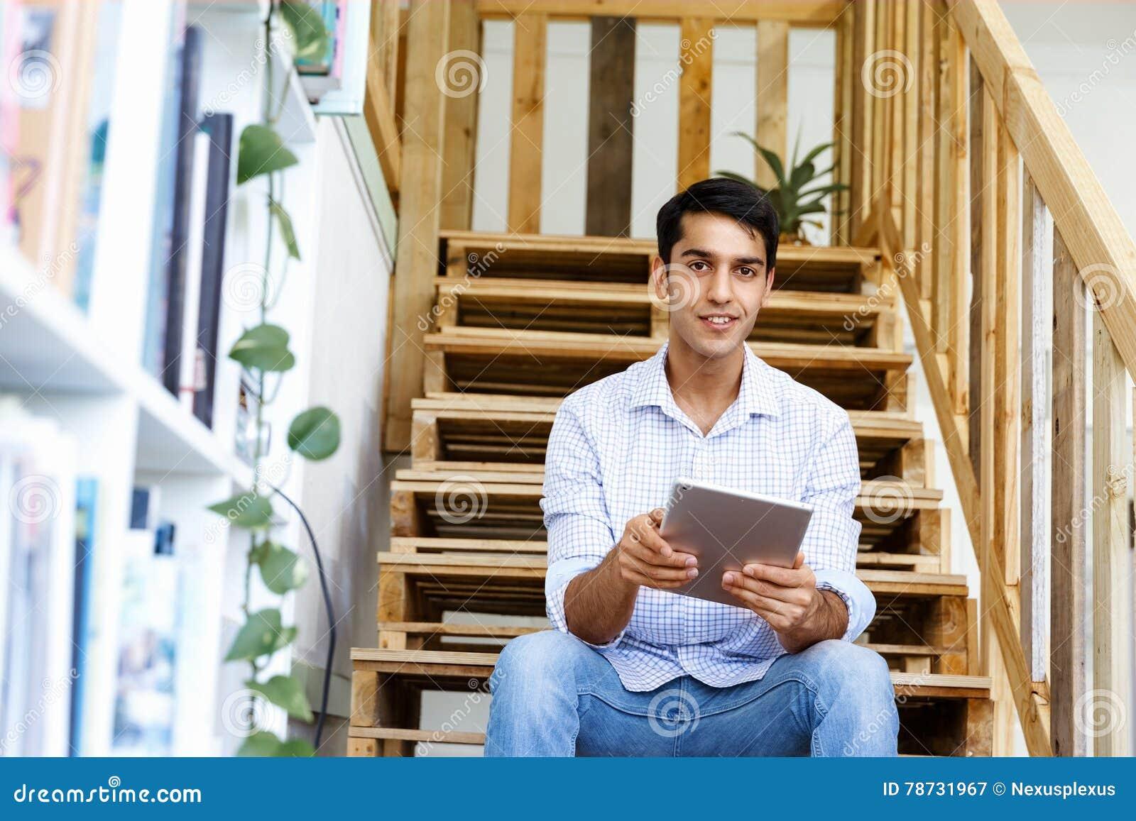 Stående av sammanträde för ung man på trappan i regeringsställning