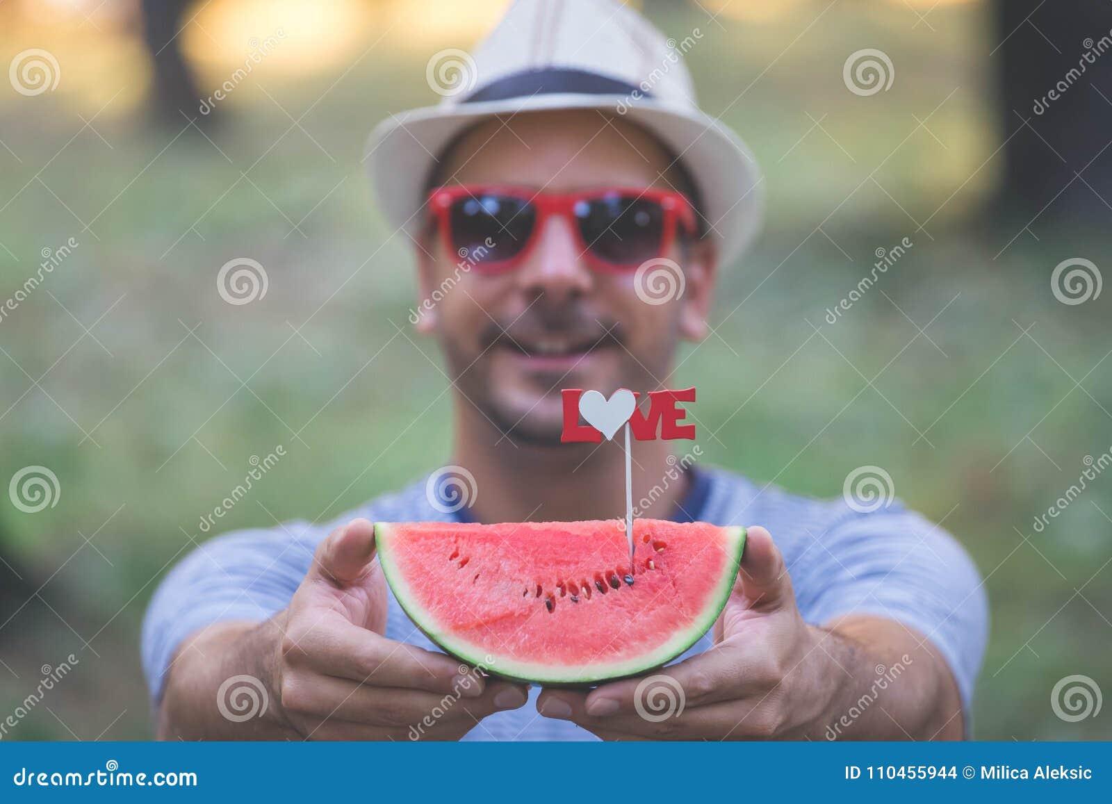 Stående av skivan för hipstergrabbinnehav av vattenmelon med förälskelsetecknet
