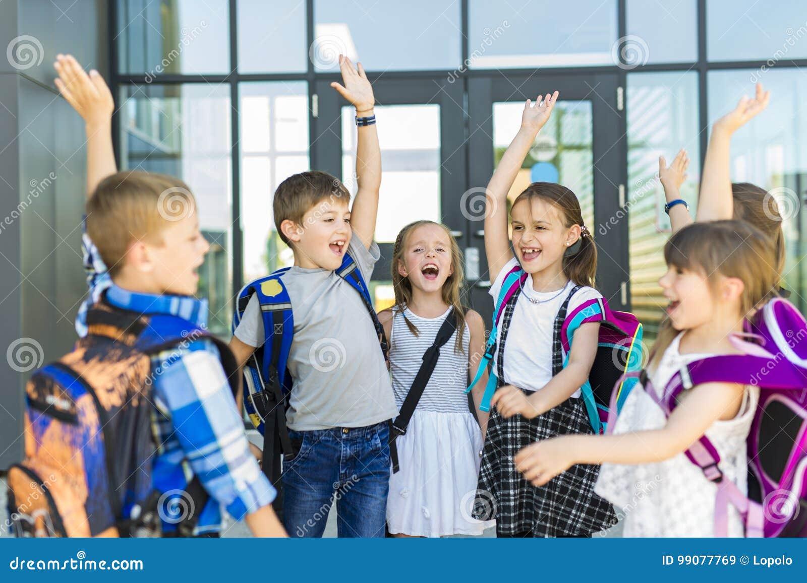 Stående av skolaelever utanför bärande påsar för klassrum