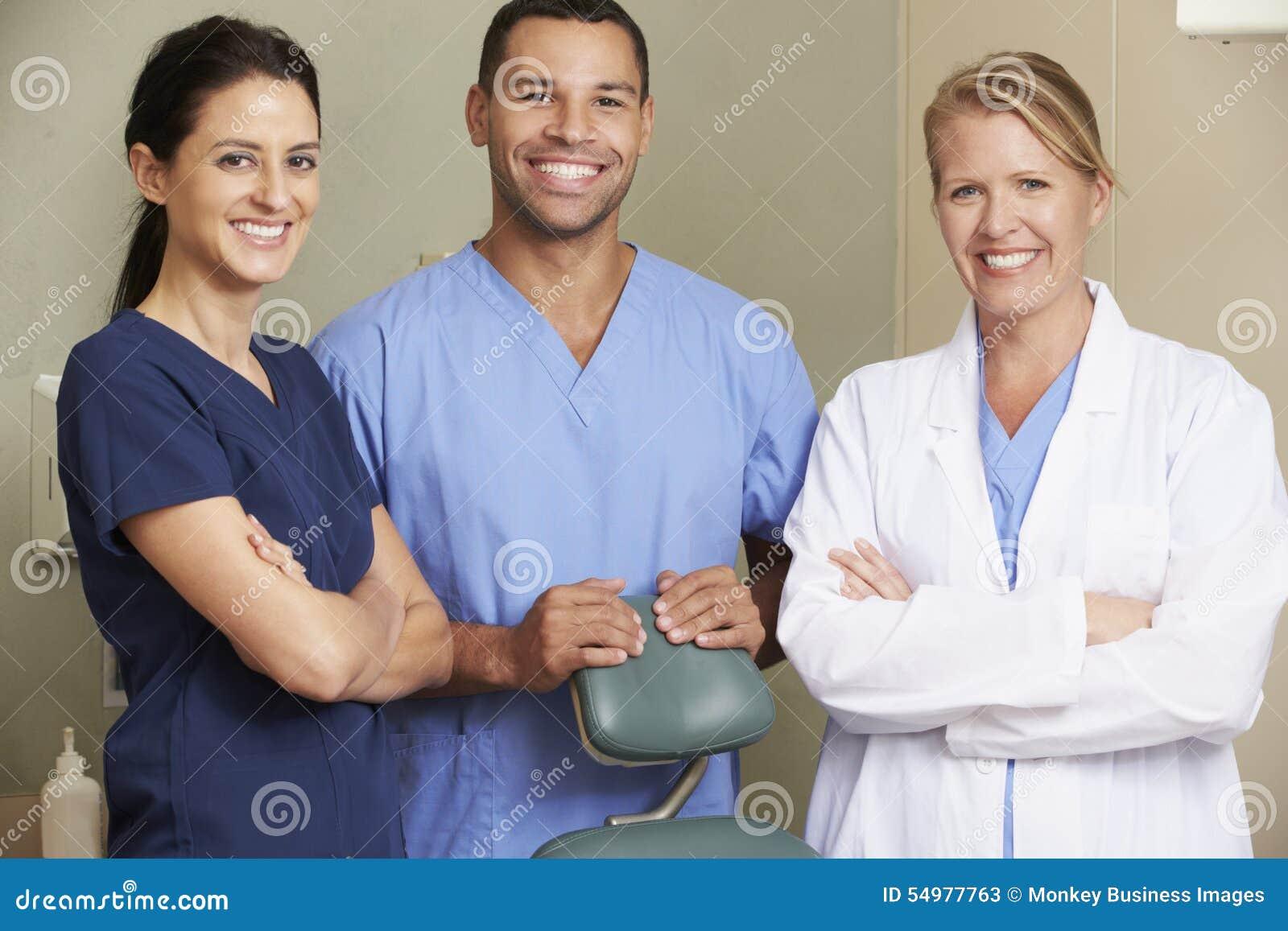 Stående av tandläkaren And Dental Nurses i kirurgi
